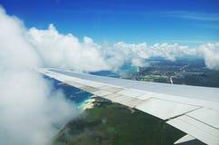 Aile d'un vol d'avion au-dessus des nuages au-dessus de l'île tropicale Photos stock