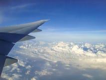 Aile d'un vol d'avion au-dessus des nuages en ciel bleu image stock