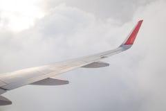 Aile d'un vol d'avion au-dessus du ciel bleu et des nuages Photos stock