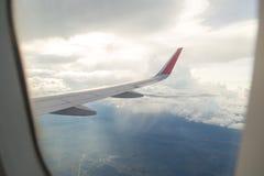 Aile d'un vol d'avion au-dessus du ciel bleu et des nuages Image libre de droits
