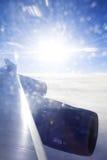 Aile de Jumbo au-dessus des nuages éclairés à contre-jour par coucher du soleil étonnant Photo stock