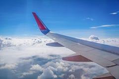 Aile du vol d'avion au-dessus des nuages dans le backgro de ciel bleu Image stock