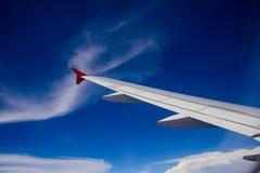 Aile du vol d'avion au-dessus des nuages dans le ciel bleu Photo stock