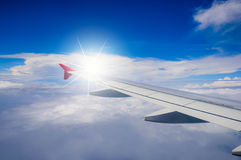Aile du vol d'avion au-dessus des nuages dans le ciel bleu Images stock