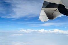 Aile du vol d'avion au-dessus des nuages et du ciel bleu Photographie stock libre de droits
