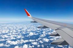 Aile du vol d'avions au-dessus des cumulus photographie stock libre de droits