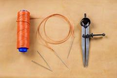 Aile et aiguille de diviseur avec le fil sur le cuir Image libre de droits