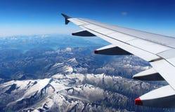 Aile plate au-dessus des Alpes avec la neige l'été de montagnes Images libres de droits