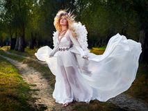 Ailes blanches de port de robe et d'ange de jeune femme photo libre de droits
