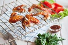 Ailes de poulet épicées chaudes de BBQ sur le gril avec de la sauce Images stock