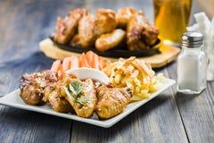 Ailes de poulet avec le sésame entouré par des fritures et des carottes Photo stock