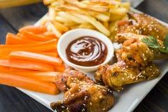 Ailes de poulet avec le sésame entouré par des fritures et des carottes Photographie stock libre de droits