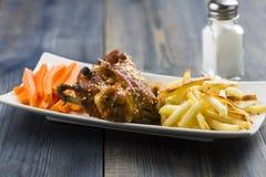 Ailes de poulet avec le sésame entouré par des fritures et des carottes Images stock