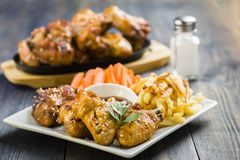 Ailes de poulet avec le sésame entouré par des fritures et des carottes Photos libres de droits