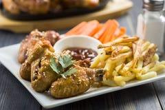 Ailes de poulet avec le sésame entouré par des fritures et des carottes Photo libre de droits