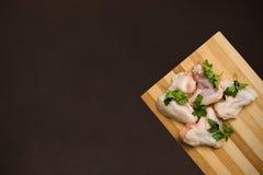 Ailes de poulet crues sur une planche à découper et une partie supérieure du comptoir foncée images libres de droits