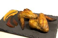 Ailes de poulet dans un tableau noir Image stock