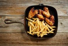 Ailes de poulet et pommes de terre frites sur la casserole de fonte photo libre de droits