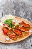 Ailes de poulet frit avec de la salade fraîche, les légumes grillés et la sauce à BBQ sur la planche à découper sur le fond en bo Photographie stock