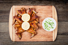 Ailes de poulet grillées délicieuses avec de la sauce à ail, citron sur une planche à découper sur la vue supérieure de fond rust Images stock