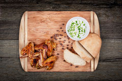 Ailes de poulet grillées délicieuses avec de la sauce à ail, des épices, des assaisonnements et le pain sur une planche à découpe Photographie stock