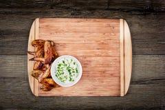 Ailes de poulet grillées délicieuses avec de la sauce à ail sur une planche à découper sur le fond rustique en bois avec la vue s Photo libre de droits