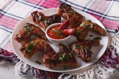 Ailes de poulet grillées savoureuses avec des poivrons de piment en gros plan horizon Image libre de droits