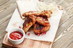 Ailes de poulet grillées Servir sur un conseil en bois sur une table rustique Menu de rôtisserie, une série de photos de Photographie stock libre de droits