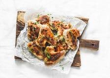 Ailes de poulet rôti sur le hachoir en bois - apéritifs délicieux, tapas sur le fond clair images libres de droits