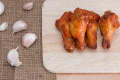 Ailes de poulet sur les planches à découper en bois avec l'ail Photos stock