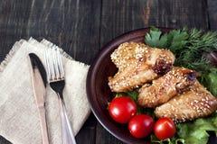 Ailes de poulet sur un panneau de portion Photos stock