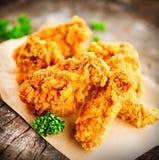Ailes et jambes de poulet frit sur la table en bois Photographie stock
