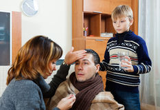 Ailing man surrounded by caring wife and son. Ailing men surrounded by caring wife and son at home stock photos