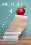 Aim high in education. Large pile of books against a blackboard with an upwards arrow royalty free stock image