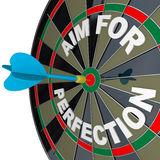Aim for Perfection - Dart Hits Target Bulls-Eye. A dart hits a target bullseye on a dartboard surrounded by the words Aim for Perfection, representing the drive Royalty Free Stock Photography