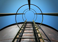 Aim for the sky. Ladder on water tank points to blue sky Stock Photo