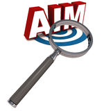 Aim. Word on blue target circle with a magnifying lens over it on white background Royalty Free Stock Photography