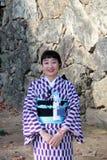 Aimable et agréable du réceptionniste dans la robe de kimono sur la couleur pourpre et blanche au château de Himeji Photo stock