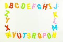 Aimants d'alphabet formant le cadre sur le tableau blanc Photos stock