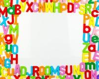 Aimants d'alphabet formant le cadre sur le tableau blanc Photographie stock libre de droits