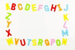 Aimants d'alphabet formant le cadre sur le tableau blanc Photo stock