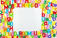 Aimants d'alphabet formant le cadre sur le tableau blanc Images libres de droits