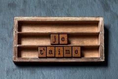 Aime de ` de Je t Je t'aime dans la traduction française La boîte de vintage, les cubes en bois expriment écrit avec des lettres  Image libre de droits
