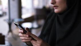 Aimed footage of female`s hands withblack smartphone. Close up of muslim woman in cafe using her smartphone, chatting stock video footage