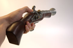 Aimed shot. Hand with aimed old gun Royalty Free Stock Images