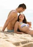 Aimer deux détendant sur la plage de sable Photos libres de droits