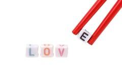 Aimez écrit dans des perles de lettre avec des baguettes tenant E Images libres de droits