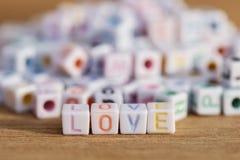 Aimez écrit dans des perles de lettre sur le fond en bois Image libre de droits