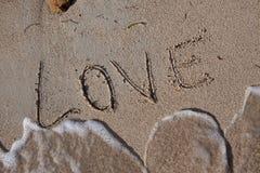 Aimez écrit en sable sur une plage des Caraïbes Image libre de droits