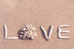 Aimez écrit par des coraux sur une plage tropicale Images libres de droits
